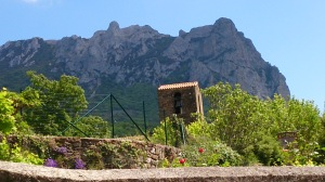 Pech de Bugarach from Bugarach village. Church bell tower in foreground
